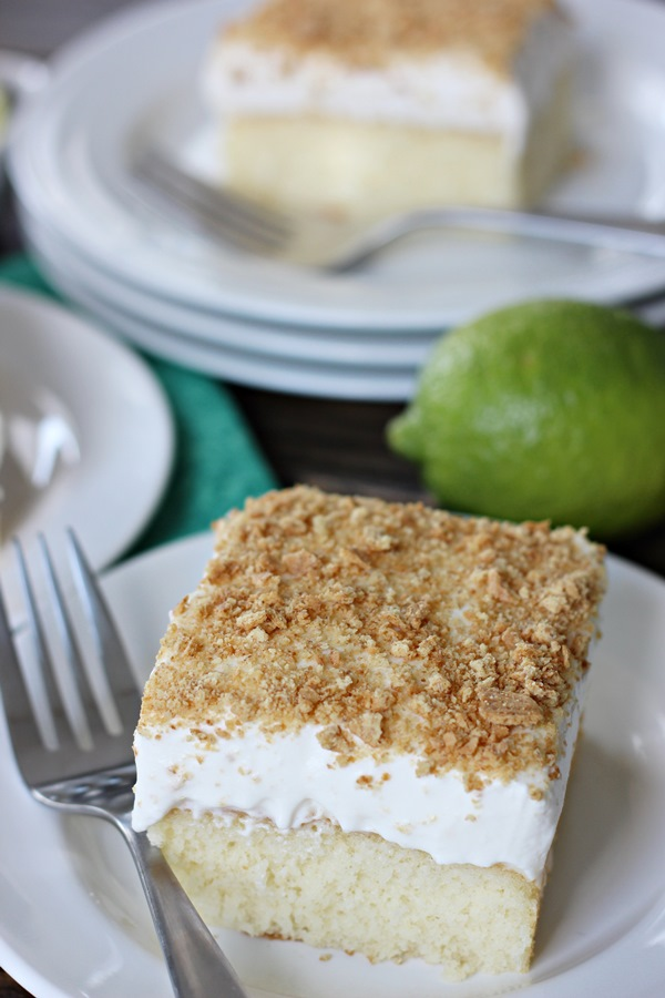 Key Lime Poke Cake – A moist and delicious white cake infused with key lime flavor and topped with a luscious whipped cream frosting and crushed graham crackers. | www.worthwhisking.com